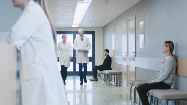 vidéos et rushes de à l'hôpital deux médecins marchant dans le couloir de l'hôpital, ils parlent et partagent des tablet pc. hôpital moderne auprès des patients et du personnel médical. - equipement médical