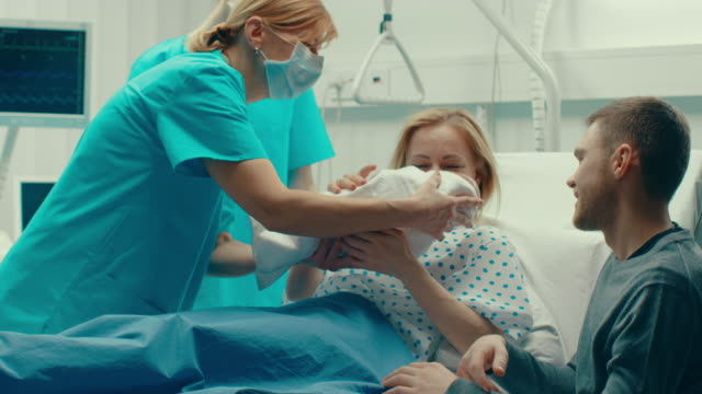 in the hospital woman in labor pushes and gives birth, baby comes out, obstetricians assist delivery, husband supports his wife. side view footage. - nowe życie filmów i materiałów b-roll