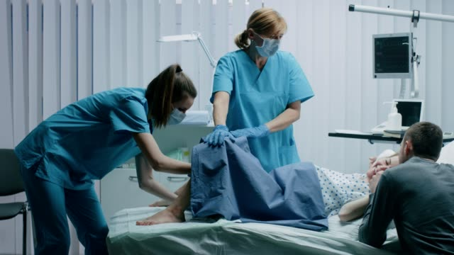 vidéos et rushes de dans la femme hôpital travail pousse à donner naissance, bébé sort, obstétriciens aider livraison, époux détient prend en charge son épouse. images de vue de côté. - naissance