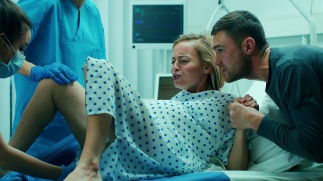 vidéos et rushes de à l'hôpital, femme en travail pousse à donner naissance, obstétriciens, aidant, conjoint détient sa main. maternité de l'hôpital moderne avec les professionnels des sages-femmes. - naissance