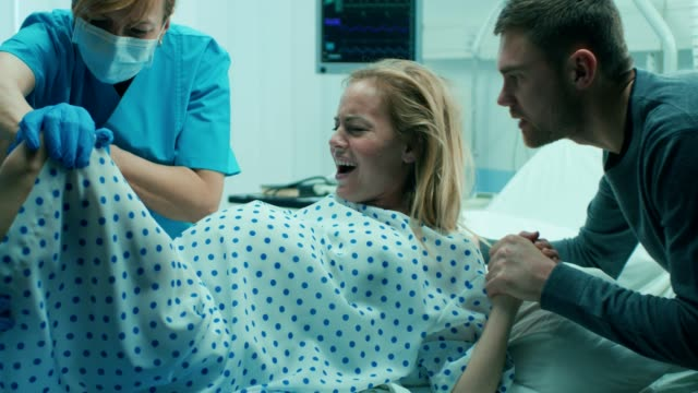 in the hospital woman in labor pushes to give birth, obstetricians assisting, husband holds her hand for support. modern delivery ward with professional midwives. - nowe życie filmów i materiałów b-roll