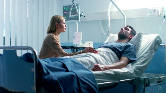 In the Hospital, Worrying Wife Sits Beside the Bed where Her Sick Husband Lies. She Holds His Hand, Talks to Him and Hopes for Recovery.