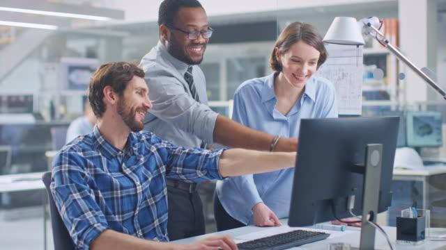 i industriell teknik facility: man ingenjör arbetar på stationär dator, kvinnlig chefs ingenjör och projektledare diskutera och förklara för honom projekt detaljer. de leende, skämt och cheer - man architect computer bildbanksvideor och videomaterial från bakom kulisserna