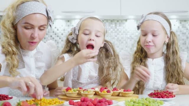 in the kitchen concept. the family decorates the pie and muffins with a berry. - bacca video stock e b–roll
