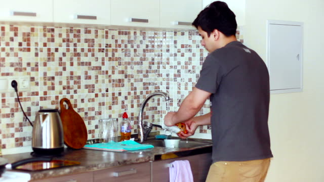 In the kitchen man wash the plates sink in t-shirt In the kitchen man wash the dishes sink in t-shirt dishwashing liquid stock videos & royalty-free footage