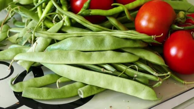 Na cozinha há feijão verde, tomate e pimenta fina, - vídeo