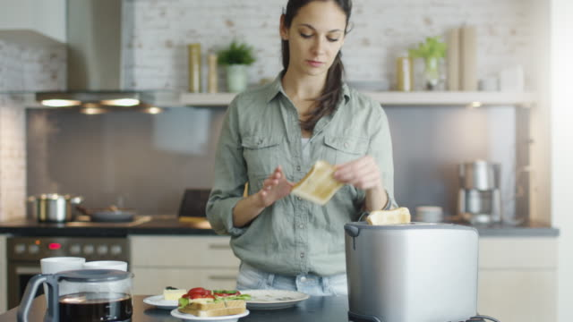 In the Kitchen Young Girl Makes Toasts and Spreads Butter on Them. video