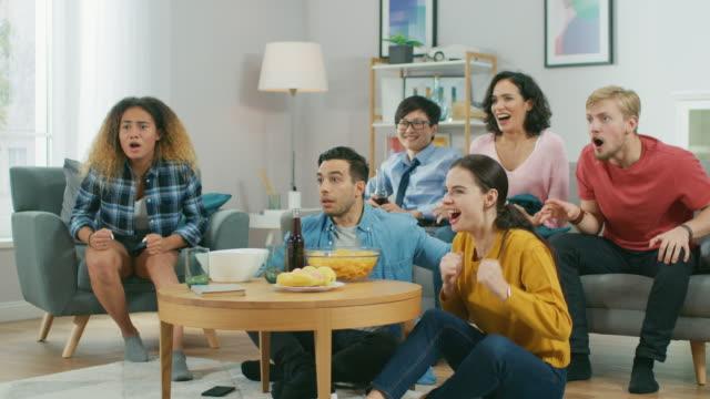 в гостиной разнообразная группа друзей по просмотру спортивных игр матч по телевизору, они развеселить и петь для команды, праздновать поб� - закуска стоковые видео и кадры b-roll