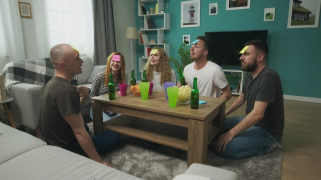 In the living room friends playing Who am I game and drinks beer video