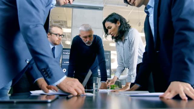 在會議室裡, 形形色色的商界人士站在桌旁, 舉行戰略規劃會議。他們使用筆記本電腦, 交流筆記和想法。 - 危機 個影片檔及 b 捲影像