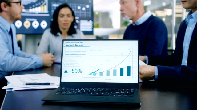 in the meeting room laptop standing on the conference desk shows company's annual growth report with interactive charts. in the background business people have important discussion. - guadagnare soldi video stock e b–roll
