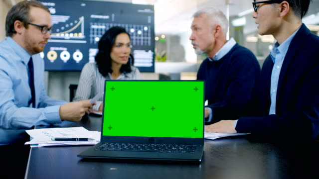 In the Meeting Room Laptop with Green Chroma Key Screen on the Conference Table. In the Background Business People Have Important Discussion.