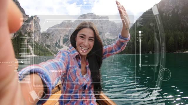 湖の真ん中で, 休日に, 女の子は、未来的なビデオ通話のために携帯電話やスマートフォンを使用しています.彼女は家から友達や家族を呼んでいます。 - ホログラム点の映像素材/bロール