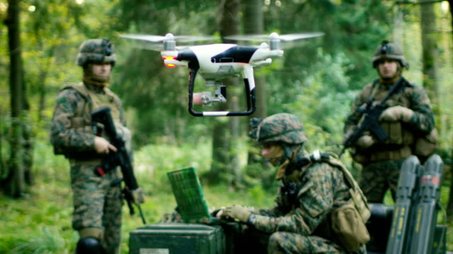 in the military staging base army engineer and soldiers fly military grade industrial drone for their reconnaisance/ surveillance mission/ operation. theater of operation is in forest area. - армия стоковые видео и кадры b-roll
