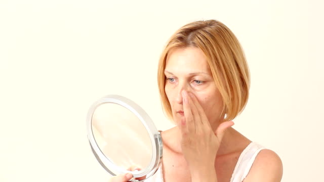 In the mirror Beautyful mature woman looking at her face in the mirror. aging process stock videos & royalty-free footage
