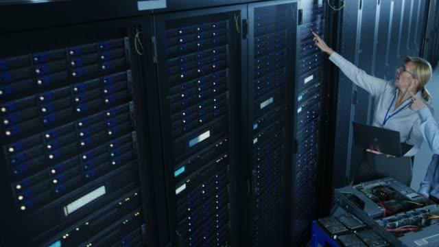 i moderna datacenter: ingenjör och it-specialist arbetar med serverrack, på en kärra utrustning för att installera ny maskinvara. specialister som gör underhåll och diagnostik av databasen. fallande kamera skott. - server room bildbanksvideor och videomaterial från bakom kulisserna
