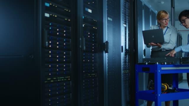 i moderna datacenter: kvinnlig ingenjör och manliga it specialist arbete med serverrack, diskutera optimeringsprocessen. på en kärra utrustning för installera ny maskinvara. specialister som gör underhåll och diagnostik av databasen. - server room bildbanksvideor och videomaterial från bakom kulisserna