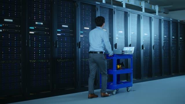 i moderna datacenter: it-ingenjör som gör underhåll och diagnostik. skjuter vagnen tillsammans med serverrack, öppnar skåp att installera ny maskinvara för planerade system update, utbyte av utrustning. - server room bildbanksvideor och videomaterial från bakom kulisserna