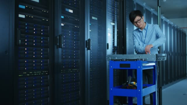 i moderna datacenter: it-ingenjör som arbetar med serverrack, använder utrustning liggande på kärra, server skåpet är öppen och redo att installera ny maskinvara för system update. - server room bildbanksvideor och videomaterial från bakom kulisserna