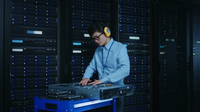 In the Modern Data Center: IT Technician Wearing Protective Headphones Working with Server Racks, on a Pushcart Installing New Hardware. Engineer Doing Maintenance and Diagnostics of the Database. In the Modern Data Center: IT Technician Wearing Protective Headphones Working with Server Racks, on a Pushcart Installing New Hardware. Engineer Doing Maintenance and Diagnostics of the Database. Shot on RED EPIC-W 8K Helium Cinema Camera. mainframe stock videos & royalty-free footage