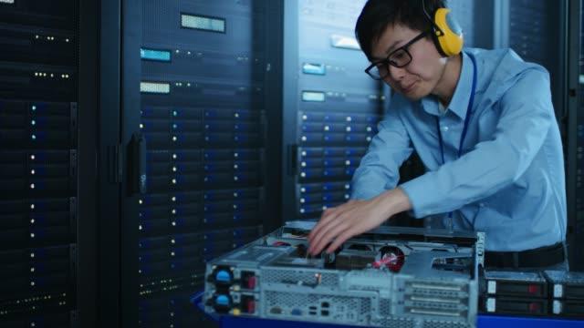 i moderna datacenter: it-tekniker som bär skyddande hörlurar arbeta med serverrack, på en kärra som installera ny maskinvara. ingenjör som gör underhåll och diagnostik av databasen. - server room bildbanksvideor och videomaterial från bakom kulisserna