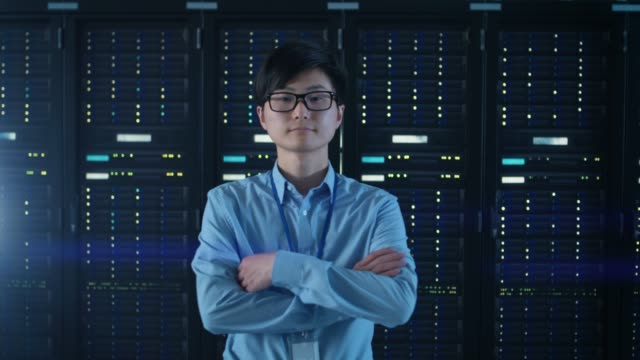 In the Modern Data Center: Portrait of IT Engineer Standing with Server Racks Behind Him, Crossing Arms. Professional IT Specialist Working in a Modern Data Center with Innovative Technologies. In the Modern Data Center: Portrait of IT Engineer Standing with Server Racks Behind Him, Crossing Arms. Professional IT Specialist Working in a Modern Data Center with Innovative Technologies. Shot on RED EPIC-W 8K Helium Cinema Camera. backup stock videos & royalty-free footage