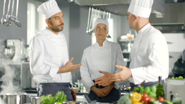 In the Modern Kitchen Team of Cooks Have Discussion. Kitchen is Full of Food Ingredients, Vegetables, Meat, Boiling Soup. video