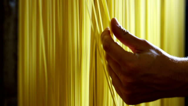 in the morning a young boy touches the hand of a fresh pasta to dry put them to ensure a high quality - pasta video stock e b–roll