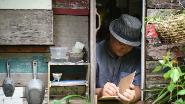 In the morning the asian man writes in the diary at the vintage window.