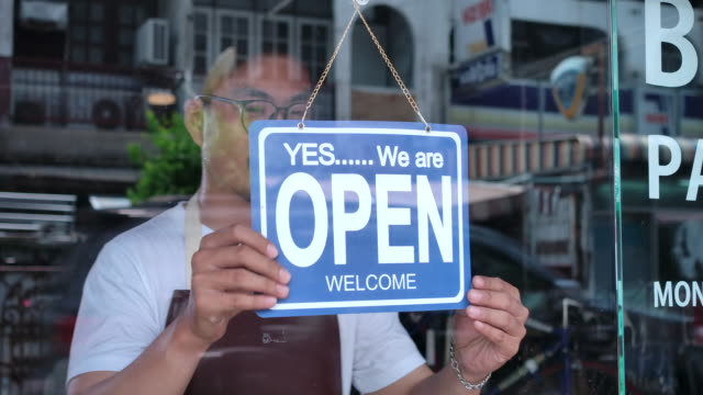 In the morning, the owner of a small business shop came to open the shop. In the morning, the owner of a small business shop came to open the shop. opening event stock videos & royalty-free footage