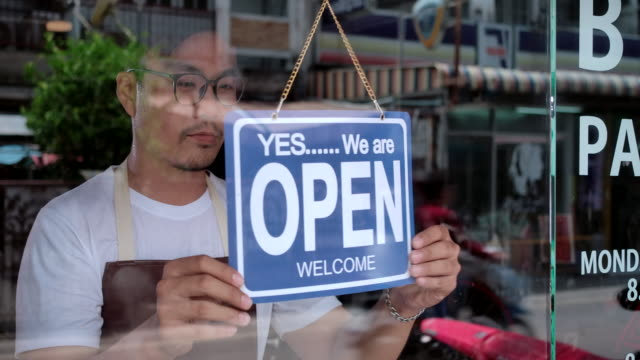 in the morning, the owner of a small business shop came to open the shop. - open sign stock videos & royalty-free footage