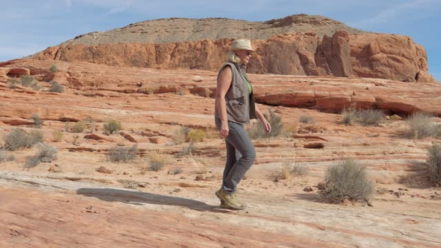 vídeos de stock e filmes b-roll de in the movement mature woman hiking on the red rock canyon - vale