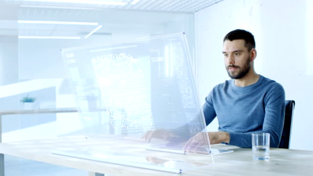 In the Near Future Man Working on His Computer with Transparent Display. Display Shows Graphic Projection of Neural Network, Artificial Intelligence Simulation. video