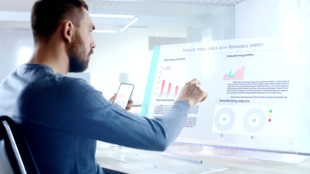 In the Near Future Renewable Energy Expert Swipes and Shares Data From Touchscreen Smartphone to His Transparent Display Computer. Screen Shows Interactive Infographics with Colorful Graphs and Data. video