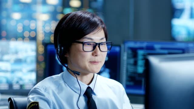 ヘッドセットとネットワーク ・ オペレーション ・ センター トレーダーは個人クライアント呼び出しで。彼はデータとグラフを示すモニターに囲まれています。 - オペレーター 日本人点の映像素材/bロール