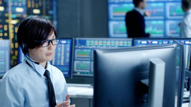 ヘッドセットとネットワーク ・ オペレーション ・ センター トレーダーは個人クライアント呼び出しで。背景のトレーダーのモニターに表示されるデータをについて説明します。 - 投資家点の映像素材/bロール