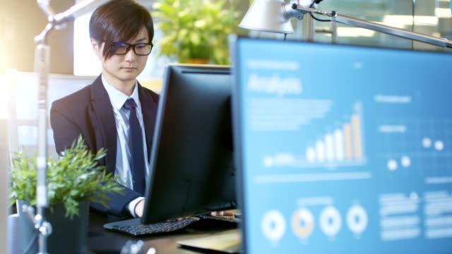 オフィスのビジネスマンと互いに逆デスクトップ パソコンの作業を座っている実業家。コンピューターの画面は、統計的成長インフォ グラフィックを示しています。 - パソコン 日本人点の映像素材/bロール