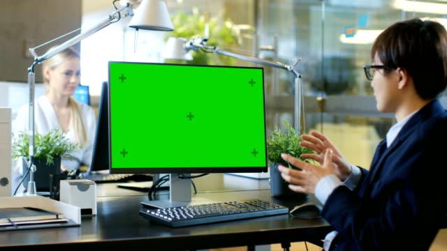 オフィスのビジネスマンにモックアップとパソコンにビデオ通話緑画面。彼は会談を受信者と積極的にリタイアします。 - オンライン会議点の映像素材/bロール