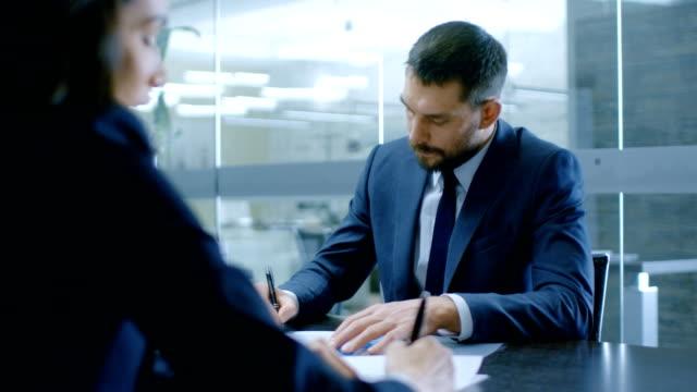 vídeos y material grabado en eventos de stock de en la oficina de empresaria y empresario tener conversación, negociación, un contrato, firmar documentos, final de la transacción, manos de la sacudida. personas con estilo en la sala de conferencias moderna. - abogado