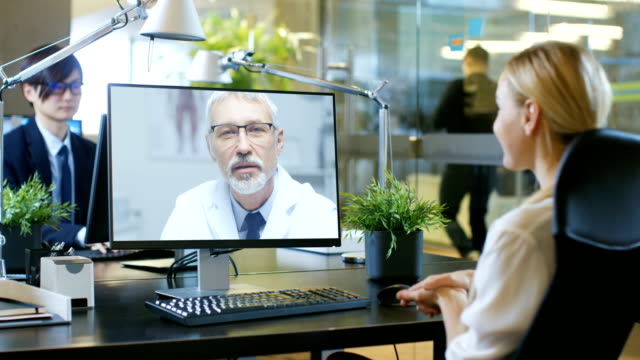in the office businesswoman talks with her doctor on the video call she made with personal computer. senior physician consults attractive blonde woman. - virtual meeting stock videos & royalty-free footage