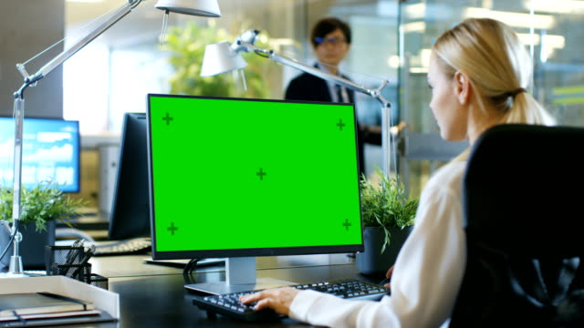 in the office businesswoman works at her desk on a personal computer with mock-up green screen. colleague enters office and takes place at his desk. - scrivania video stock e b–roll