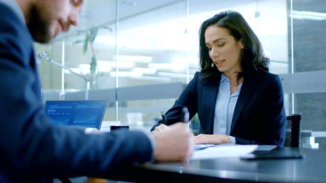 vídeos de stock, filmes e b-roll de no escritório um close na empresária e empresário ter conversa, negociar, redigir um contrato, assinar documentos, terminar a transação, apertar as mãos. pessoas elegantes na moderna sala de conferências. - dia do cliente