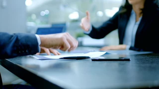in the office close-up on hands of businesswoman and businessman while signing contracts and shaking hands for finishing transaction. stylish people in modern conference room. - firma video stock e b–roll