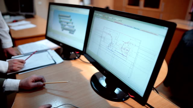 In the office engineers review and discuss the details in the diagrams