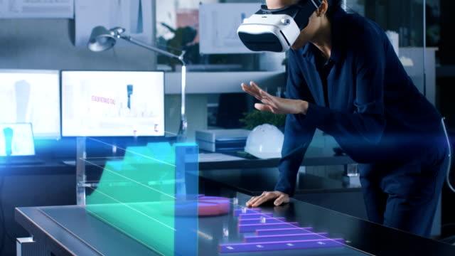 office profesyonel kadında artar gerçeklik kulaklık giyen istatistikleri gösteren infographics ile etkileşime girer.  animasyonlu 3d modelleri gösteren şirketin büyüme ile masada eğilir. - sanal gerçeklik stok videoları ve detay görüntü çekimi