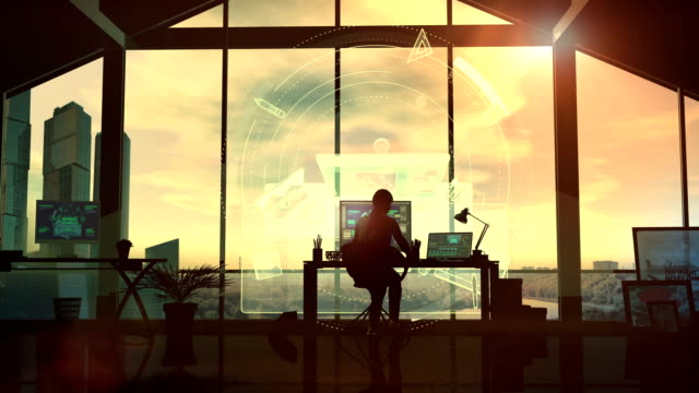 In the office, the silhouette of a female designer at the desk.