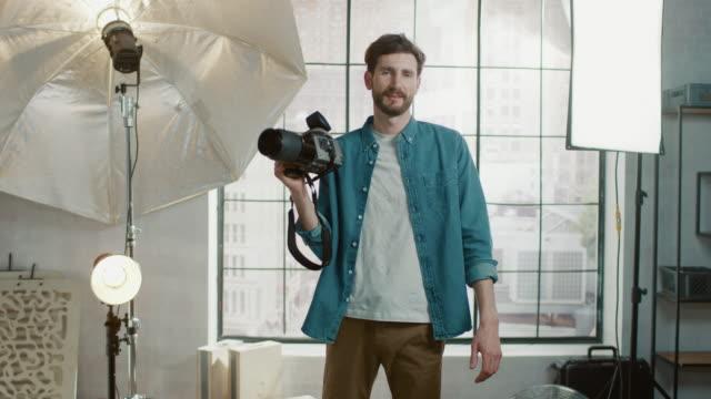 nello studio fotografico con attrezzature professionali: ritratto del bel fotografo che tiene la fotocamera all'avanguardia pronta a scattare foto con illuminazione softboxes in background - fotografia immagine video stock e b–roll