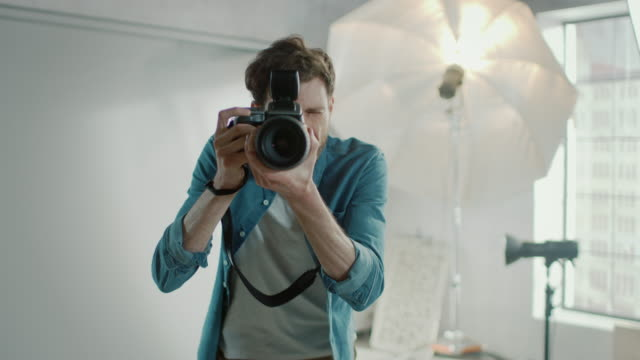 In the Photo Studio with Professional Equipment.: Portrait of the Famous Photographer Holding State of the Art Camera Taking Pictures with Softboxes Flashing in Background. In Slow Motion