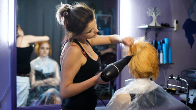 In the professional salon hairstyle on the girl's head dried hairdryer video