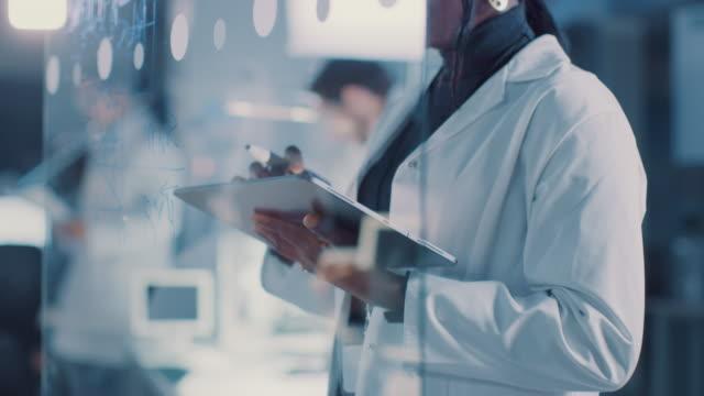 vídeos de stock, filmes e b-roll de no laboratório de pesquisa esperto e o revestimento branco desgastando do cientista fêmea africano bonito e os vidros protetores escrevem a fórmula no whiteboard de vidro, referências seu computador da tabuleta - biotecnologia